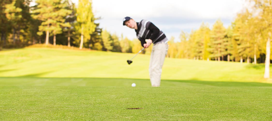 Erik puttar golfboll på green